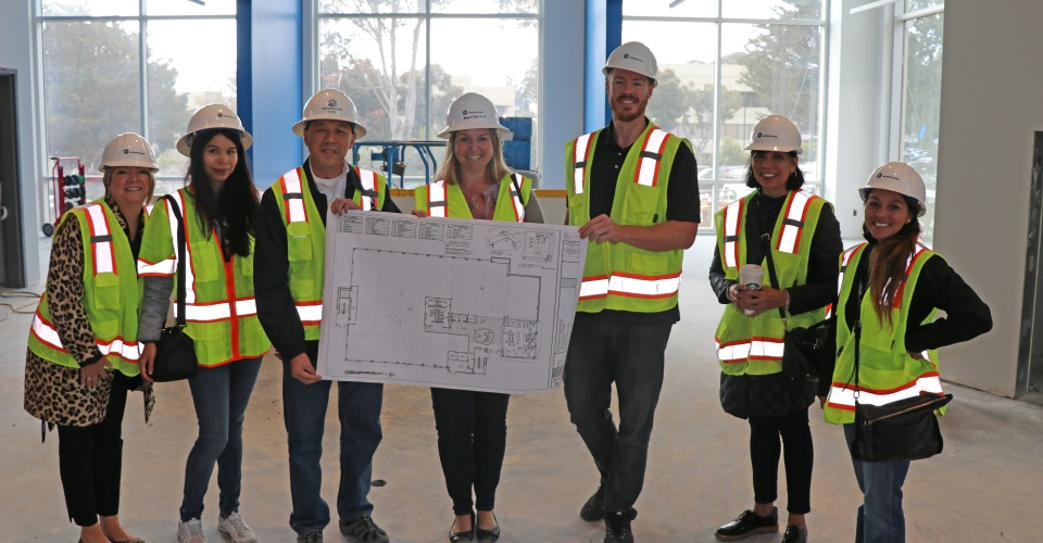Group photo of team members holding building plans