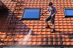 Worker cleaning a gutter