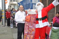 Santa Claus holding a large stocking filled with toys