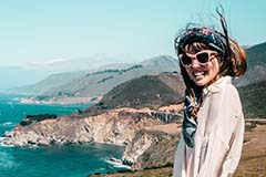 Smiling girl with sunglasses posing at Bixby Bridge in Big Sur