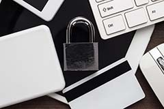 A picture of a padlock among credit cards, laptops, and phones