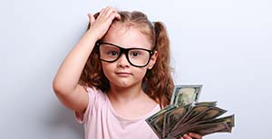 A young girl wearing big glasses and holding dollar bills
