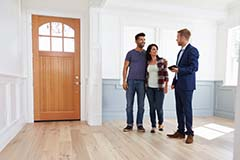 A realtor talking to a young man and woman in the entryway of a new home