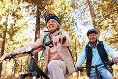A senior couple riding bikes in a wooded area