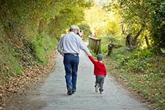 A grandfather and his grandson walking on a nature trail