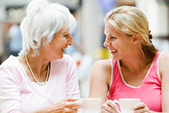 A grandmother and granddaughter laughing and having coffee together