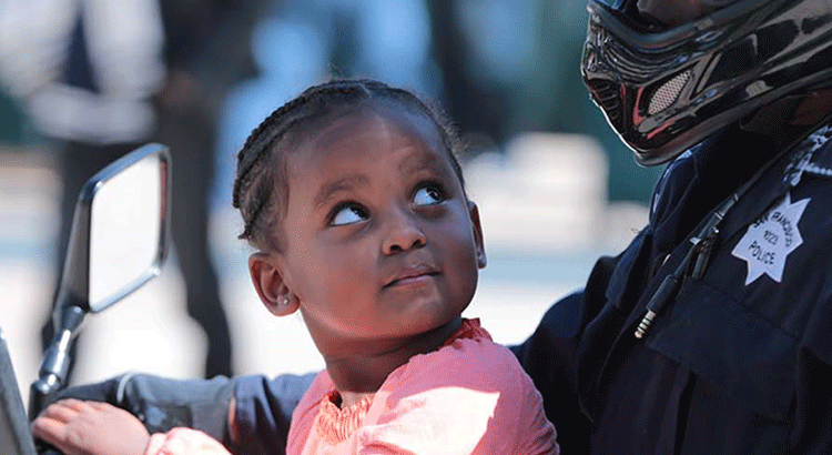 A young girl looks at an SFPD motorcycle officer